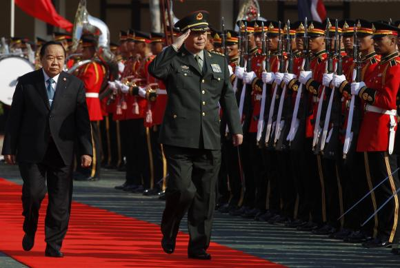 Chang reviews a guard of honour at the Defence Ministry in Bangkok